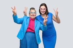 Oudere vrouw met kleinkind die vredesteken tonen royalty-vrije stock afbeeldingen
