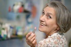 Oudere vrouw met lippenstift royalty-vrije stock afbeelding
