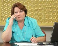 Oudere vrouw op de telefoon bij haar bureau Royalty-vrije Stock Afbeeldingen