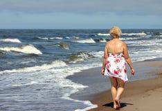 Oudere vrouw op het strand stock foto