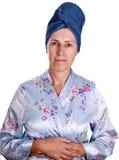Oudere vrouw in peignoir die over wit wordt geïsoleerdl Stock Foto