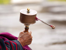 Oudere vrouwen die haar gebedwiel spinnen Royalty-vrije Stock Fotografie