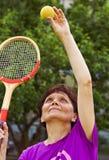 Oudere vrouwenspelen met een een tennisbal en racket Op de Speelplaats in de zomer Stock Fotografie