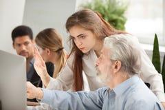 Oudere werknemer die jonge managervraag stellen over online comput stock afbeeldingen