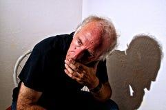Oudere witte mens die weg in gedachte kijken Stock Foto