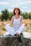 Oudere yogavrouw die voor geestelijke vrede zoeken Royalty-vrije Stock Afbeeldingen