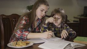 Oudere zuster en jongere broer die thuiswerk doen die samen bij de lijst thuis zitten De tiener die weinig helpen stock video