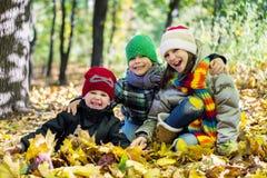 Oudere zuster en twee jongere broers in Gelukkige de herfstbladeren Stock Fotografie