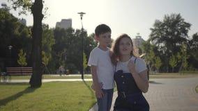 Oudere zuster het besteden tijd met het jongere broer babbelen in het de zomerpark Vrije tijd in openlucht Vriendschappelijke rel stock footage