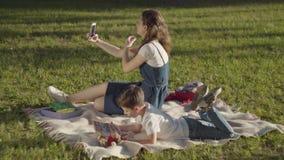Oudere zuster het besteden tijd met jongere broer in openlucht De jongen het boek lezen en meisje die selfie in het park nemen stock footage