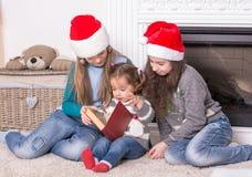 Oudere zusters die een Kerstmisverhaal zijn kleine zuster lezen Stock Foto