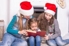 Oudere zusters die een Kerstmisverhaal zijn kleine zuster lezen Stock Foto's