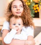 Oudere zusterzitting op trap met jongere zuster De liefdeconcept van de familie stock afbeeldingen