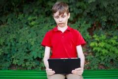 Ouderlijke adviserend Overweldigde verwarde jongenszitting met binnen tablet royalty-vrije stock afbeeldingen