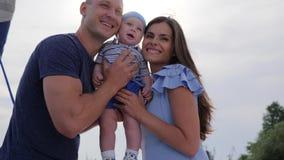 Ouderlijke kus voor baby in zonlicht, goed stemmings jong echtpaar met zoon in openlucht, gelukkig kind in handen van mamma stock videobeelden