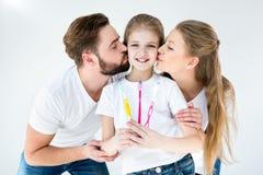 Ouders die de leuke tandenborstels van weinig dochterholding kussen royalty-vrije stock fotografie