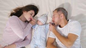 Ouders die dichtbij slaapbaby liggen stock video