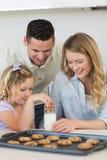 Ouders die dochter onderdompelend koekje bekijken in melk stock afbeelding