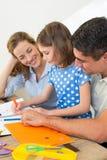 Ouders die dochterkleuring bekijken Royalty-vrije Stock Afbeeldingen
