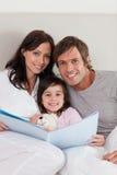 Ouders die een verhaal lezen aan hun dochter Stock Afbeeldingen