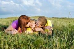 Ouders die hun dochter kussen die op een groene weide liggen royalty-vrije stock afbeelding