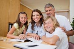 Ouders die hun kinderen met thuiswerk helpen Royalty-vrije Stock Afbeelding