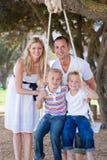 Ouders die hun kinderen op een schommeling duwen Royalty-vrije Stock Foto