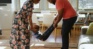 Ouders die hun zoon in een comfortabel huis 4k slingeren stock footage