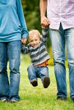 Ouders die hun zoon opheffen Royalty-vrije Stock Afbeeldingen
