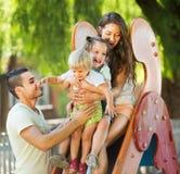 Ouders die jonge geitjes op dia helpen Stock Fotografie