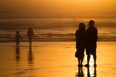 Ouders die jonge geitjes op silhouetten letten bij zonsondergang op strand Stock Afbeeldingen