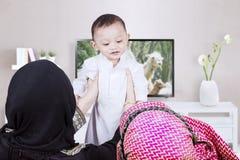 Ouders die jongen in woonkamer opheffen Royalty-vrije Stock Foto's
