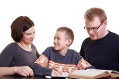 Ouders die kind met thuiswerk helpen Stock Afbeeldingen