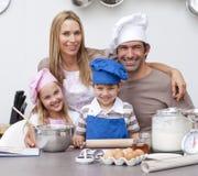 Ouders die kinderen helpen die in de keuken bakken Royalty-vrije Stock Fotografie