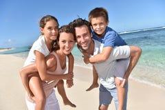 Ouders die kinderen op hun rug op het strand vervoeren Stock Foto's