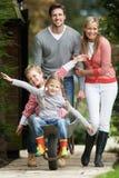 Ouders die Kinderenrit in Kruiwagen geven Stock Fotografie