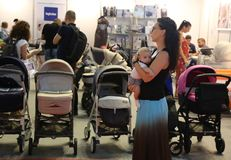 Ouders die kinderwagens bekijken Stock Afbeeldingen