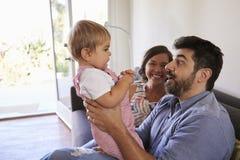 Ouders die met Babydochter spelen op Sofa At Home stock afbeelding