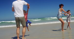 Ouders die met hun jonge geitjes bij strand spelen stock video