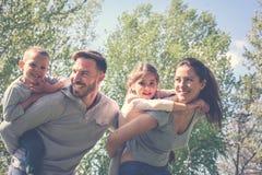 Ouders die met hun kinderen in het park spelen Stock Afbeeldingen