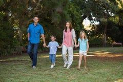 Ouders die met hun twee kinderen lopen Stock Foto's