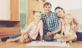 Ouders die met jonge geitjes thuis spelen Royalty-vrije Stock Afbeelding