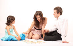 Ouders die mikado met hun kleine dochter spelen stock fotografie