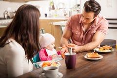 Ouders die ontbijt met babymeisje eten Stock Afbeelding