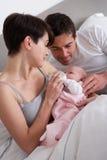 Ouders die Pasgeboren Baby in Bed voeden Stock Fotografie