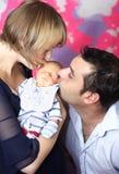 Ouders die pasgeboren baby kussen Stock Foto