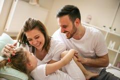 Ouders die pret met hun kleine dochter op bed hebben Royalty-vrije Stock Foto