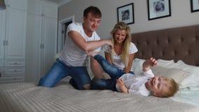 Ouders die pret met hun kleine dochter op bed hebben Familie het besteden tijd bij de ochtend stock footage