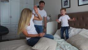 Ouders die pret met hun kleine dochter op bed hebben Familie het besteden tijd bij de ochtend stock video