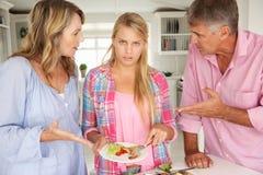 Ouders die tienerdaughter do chores thuis maken stock afbeelding
